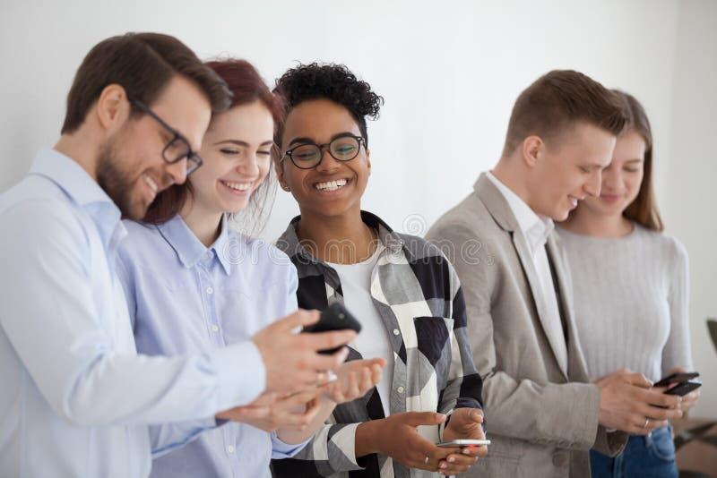 Glücklicher verschiedener Stand der jungen Leute in der Reihe unter Verwendung der Smartphones lizenzfreie stockfotografie