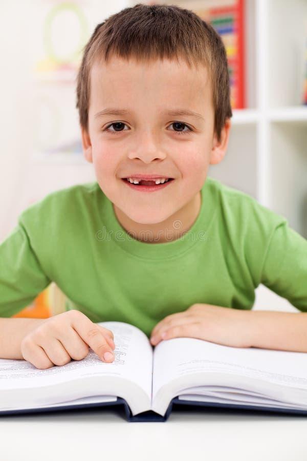 Glücklicher Volksschulejungenpraxismesswert stockfoto