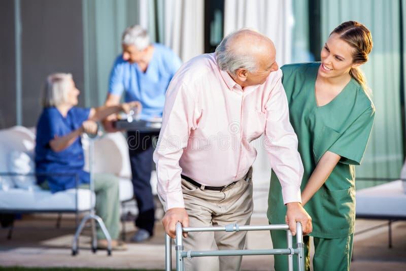 Glücklicher Wärter, der älteren Mann bei der Anwendung unterstützt stockfotografie