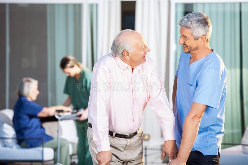 Glücklicher Wärter mit behindertem älterem Mann am Yard lizenzfreies stockbild