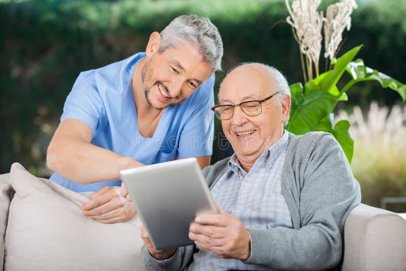 Glücklicher Wärter und älterer Mann, der Tablet-PC verwendet lizenzfreie stockfotos