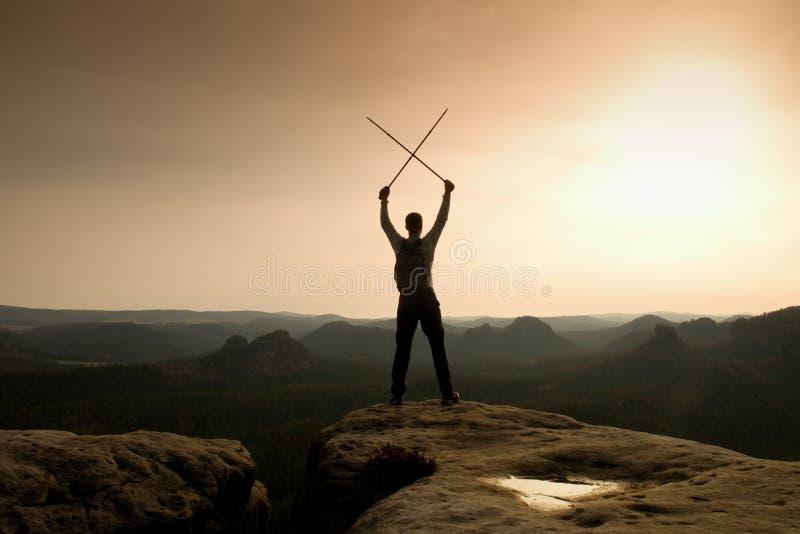 Glücklicher Wanderer mit x gekreuzten Pfosten in der Luft, offene nebelhafter Gebirgstalgebrüllklippe Schattenbild des Touristen lizenzfreie stockfotografie