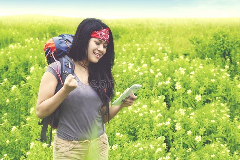 Glücklicher Wanderer mit Smartphone auf dem Blumengebiet stockfoto