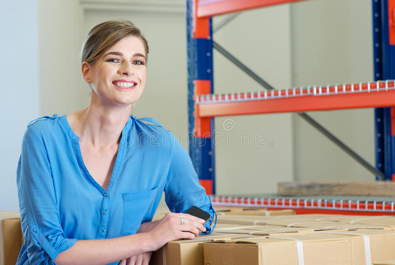 Glücklicher Weiblicher Angestellter, Der Im Lager Lächelt Lizenzfreie Stockbilder