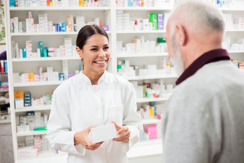 Glücklicher weiblicher Apotheker, der dem älteren männlichen Kunden Medikationen gibt stockbilder