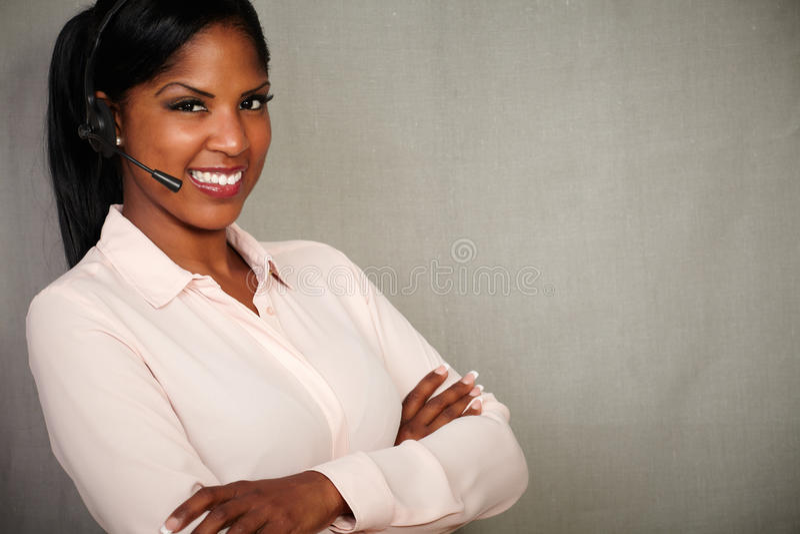 Glücklicher weiblicher Betreiber, der an der Kamera lächelt stockfotografie