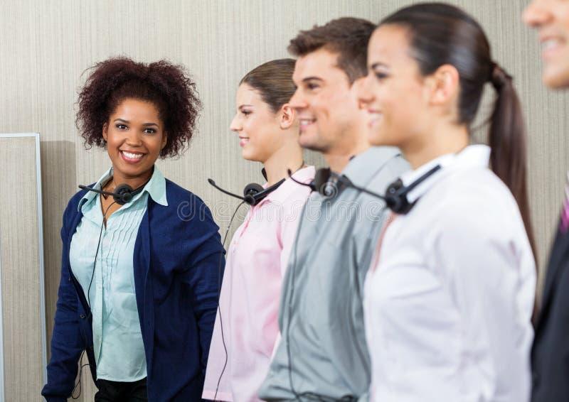 Glücklicher weiblicher Call-Center-Angestellter, der mit steht stockfoto