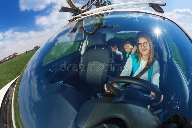 Glücklicher weiblicher Fahrer, der mit dem Auto mit Kindern reist stockfotos
