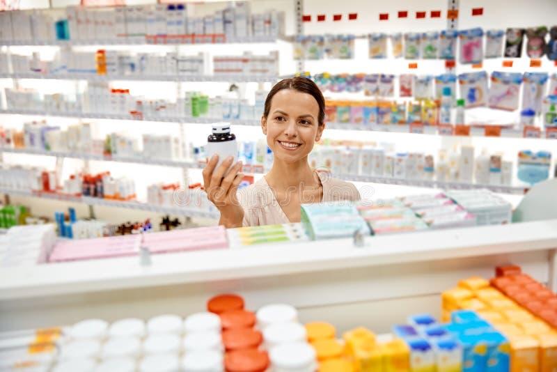 Glücklicher weiblicher Kunde mit Drogenglas an der Apotheke lizenzfreie stockfotos