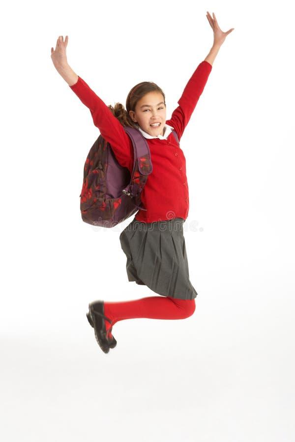 Glücklicher weiblicher Kursteilnehmer in der Uniform, die in einer Luft springt stockfoto