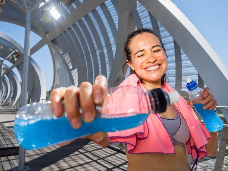 Glücklicher weiblicher Läufer mit Energiegetränken für Hydratation lizenzfreie stockbilder