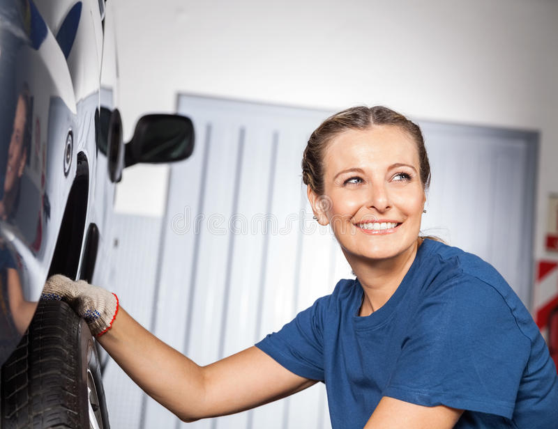 Glücklicher weiblicher Mechaniker Fixing Car Tire lizenzfreies stockbild
