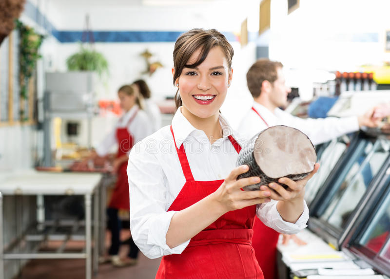 Glücklicher weiblicher Metzger Holding Large Ham lizenzfreie stockbilder