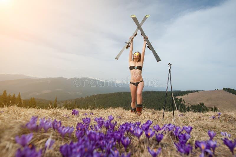 Glücklicher weiblicher Skifahrer genießt warmen Frühling, tragenden Badeanzug, Stiefel und Sonnenbrille stockfotos