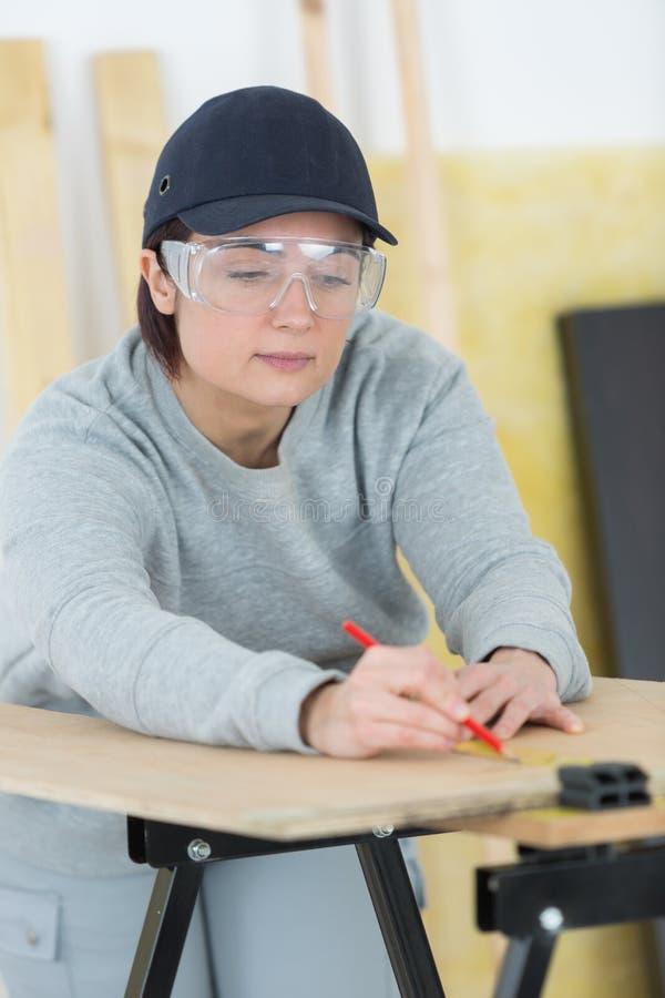 Glücklicher weiblicher Tischler des Porträts, der neues Projekt an der Werkstatt zeichnet stockfotos