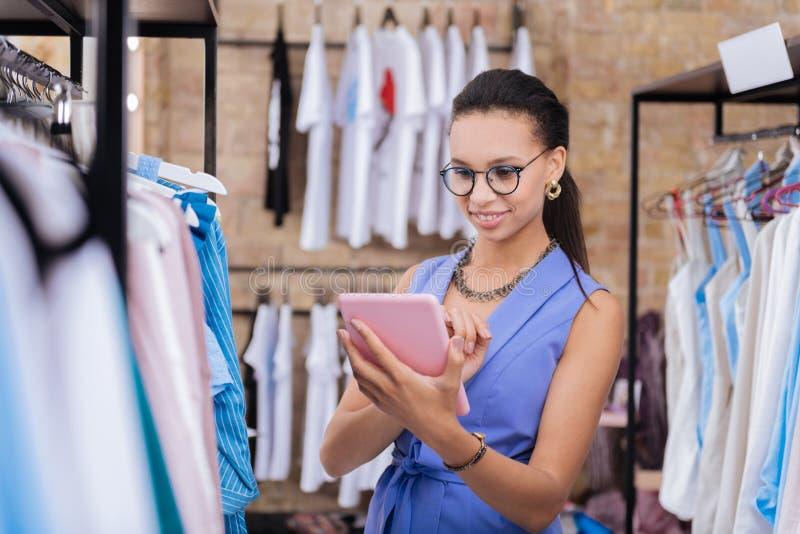 Glücklicher weiblicher Verkaufsassistent, der Produktfunktionen beschreibt stockbilder