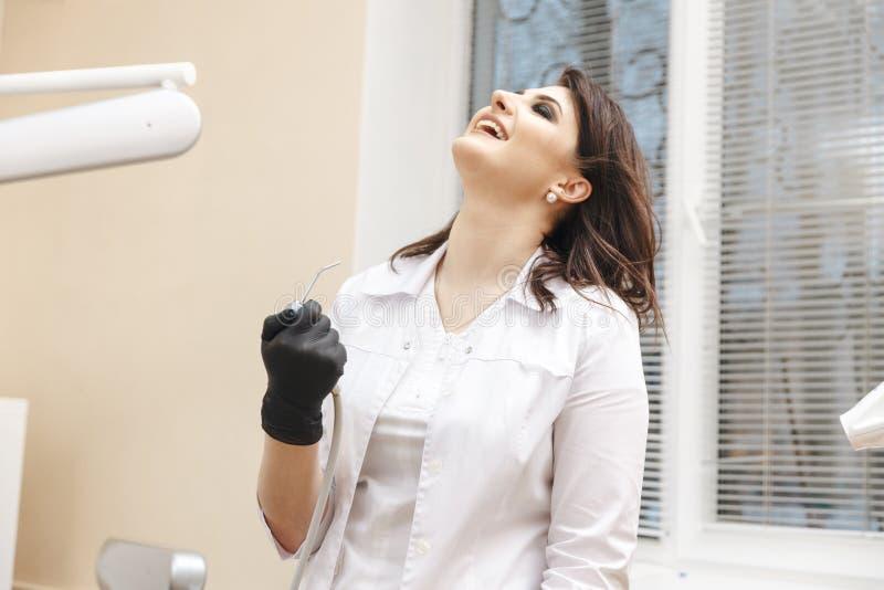 Glücklicher weiblicher Zahnarzt, der das Werkzeug hält und im Kabinett lacht stockfotos
