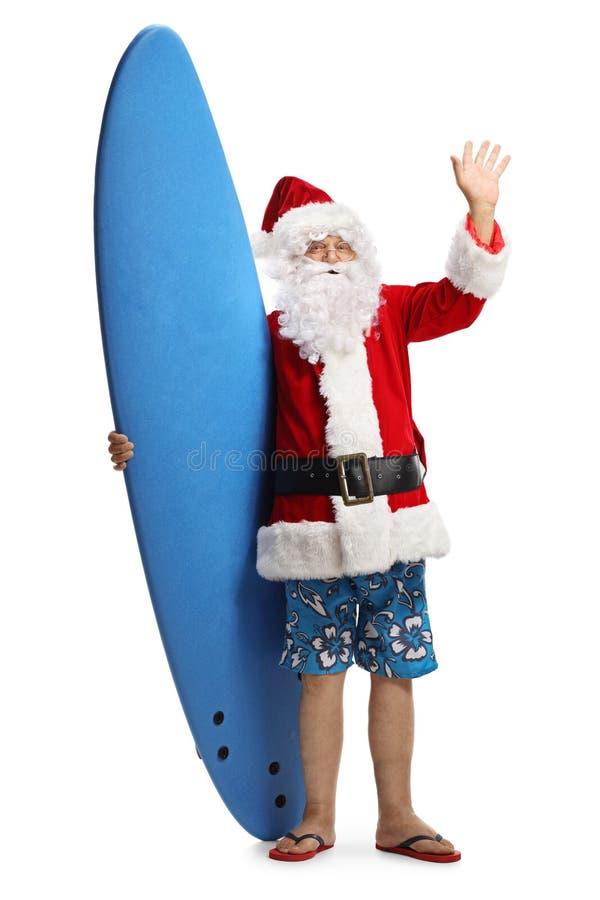 Glücklicher Weihnachtsmann an einem Feiertag mit einem Surfbrett, das an der Kamera wellenartig bewegt stockfoto