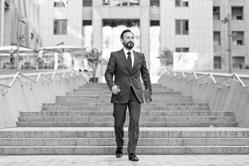 Glücklicher Wirtschaftler geht unten in Eilbewegung Junges zeitgenössisches Geschäftsmanngehen im Freien in der Stadt, mit ipad h lizenzfreie stockfotos