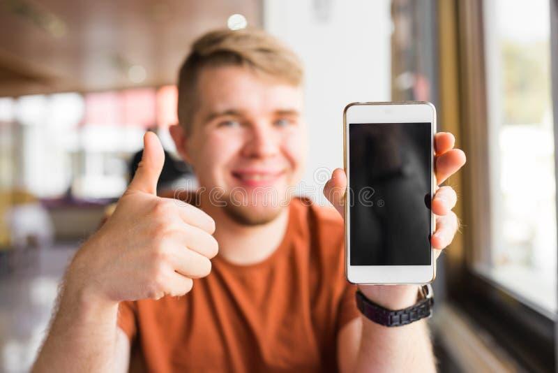 Glücklicher zufälliger Mann, der sich leeren Smartphoneschirm und -daumen zeigt stockfotografie