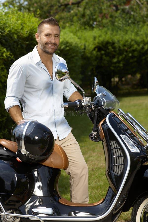 Glücklicher zufälliger Mann mit elegantem schwarzem Roller lizenzfreies stockfoto