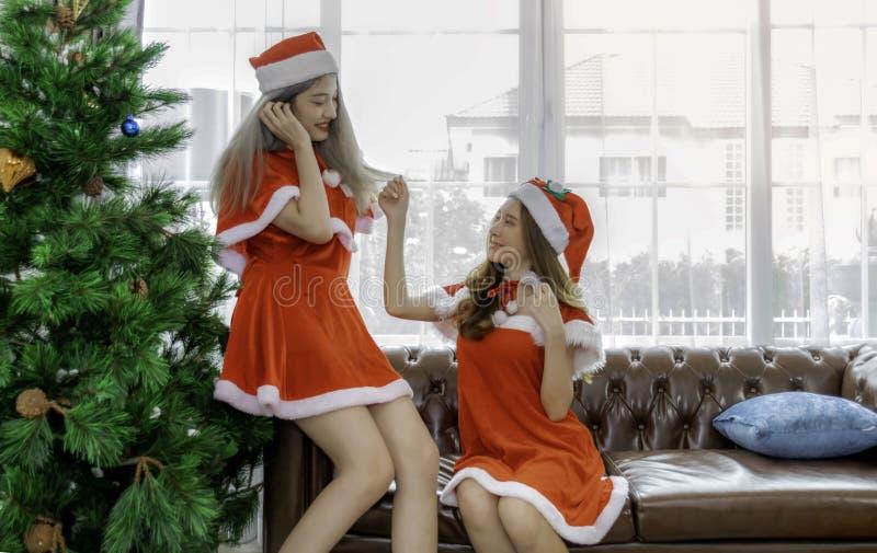 Glücklicherweise tragen zwei schöne Frauen Weihnachtskleidung, die einander zu Weihnachten erzürnen selektiver Fokus stockfotos