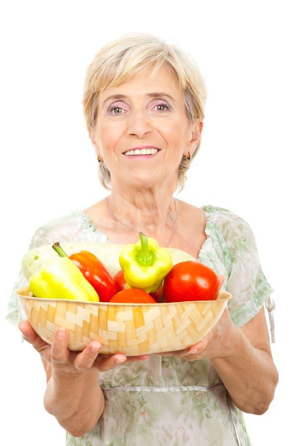 Glückliches älteres Frauenholdinggemüse stockfotografie
