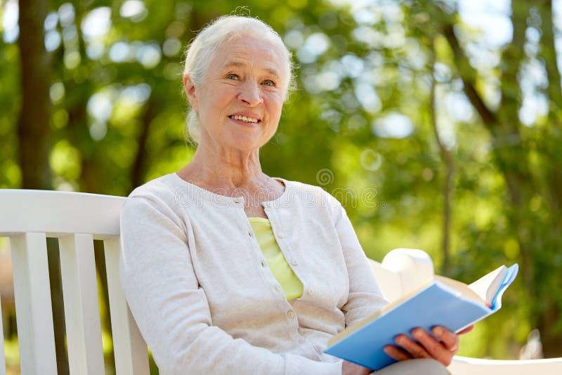Glückliches älteres Frauenlesebuch am Sommerpark lizenzfreie stockfotografie