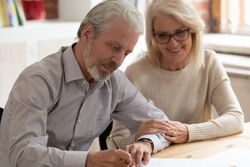 Glückliches älteres legales Papier des Familienpaarehemann- und -frauzeichens lizenzfreies stockbild