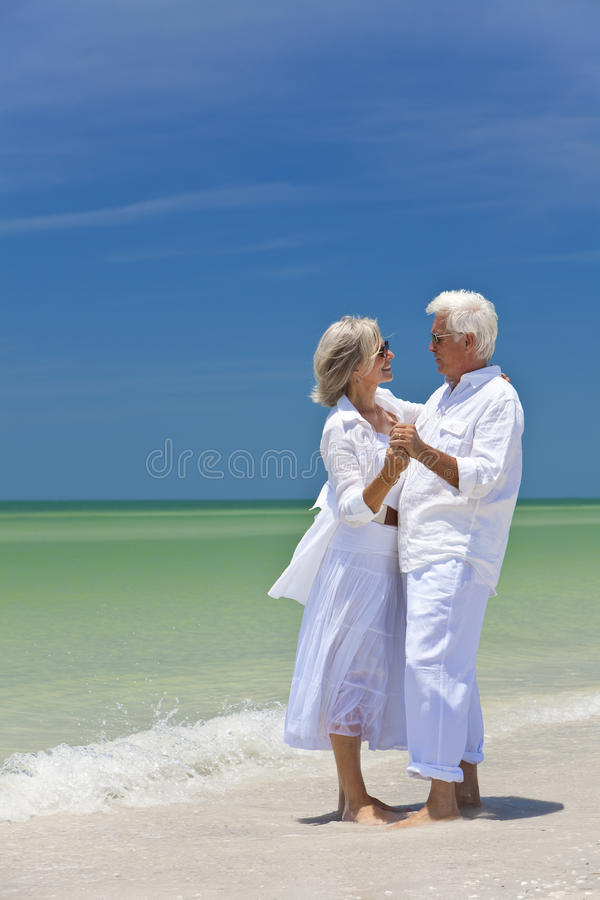 Glückliches älteres Paar-Tanzen auf einem tropischen Strand lizenzfreie stockfotos