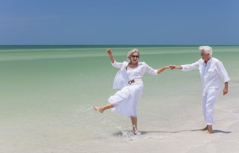 Glückliches älteres Paar-Tanzen, das Hände auf einem tropischen Strand anhält lizenzfreies stockfoto