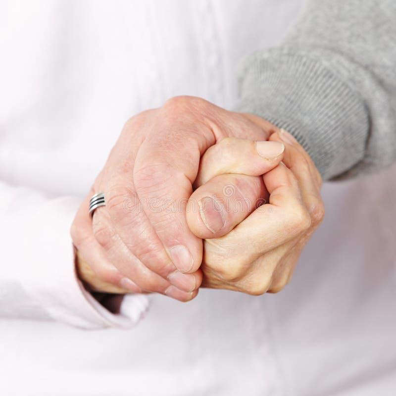 Glückliches älteres Paarhändchenhalten stockbild