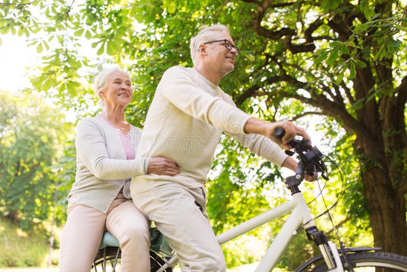 Glückliches älteres Paarreiten auf Fahrrad am Park lizenzfreies stockbild