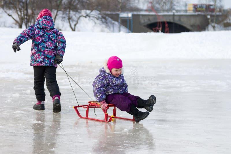 Glückliches Ältestmädchen, das ihre junge Schwester auf einem Schlitten auf dem Eis im Park des verschneiten Winters zieht stockbild