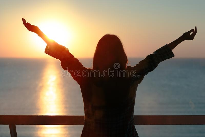 Glückliches überzeugtes Frauenschattenbild mit den offenen Armen im Morgensonnenaufgang lizenzfreies stockfoto