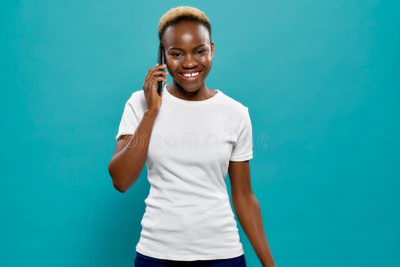 Glückliches afrikanisches Frauenholdingtelefon zum Ohr lizenzfreie stockbilder