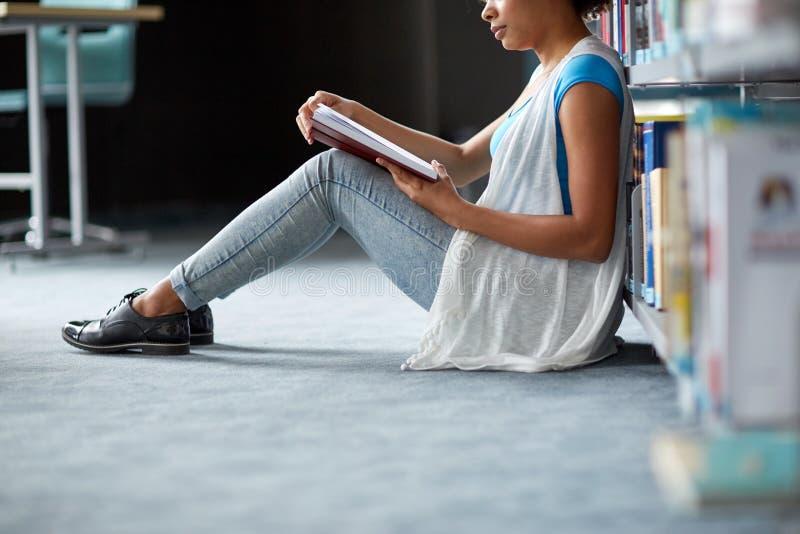 Glückliches afrikanisches Studentenmädchen-Lesebuch an der Bibliothek lizenzfreies stockfoto