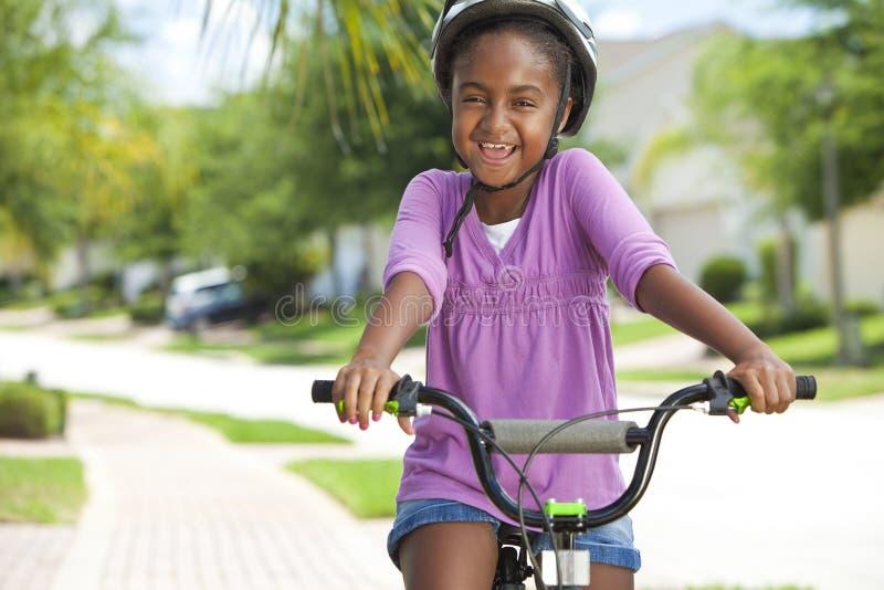 Glückliches Afroamerikaner-Mädchen-Reitfahrrad-Lächeln stockfoto