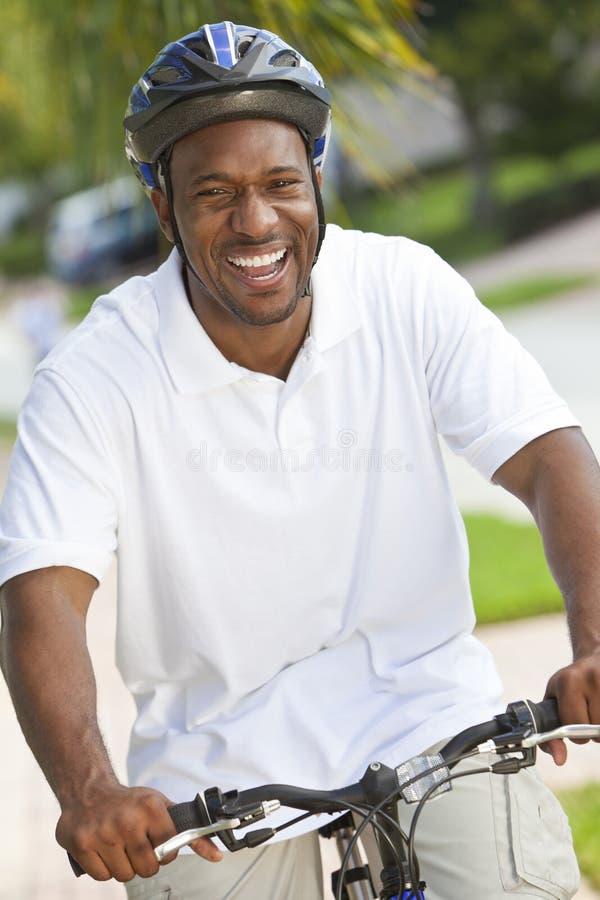 Glückliches Afroamerikaner-Mann-Reitfahrrad-Lächeln stockbilder