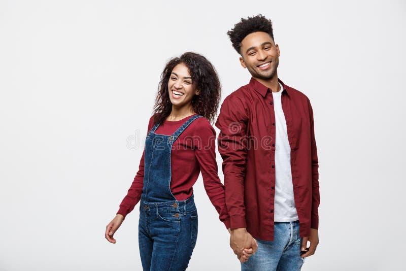 Glückliches Afroamerikanerpaarhändchenhalten und Schauen zurück lokalisiert auf Weiß lizenzfreie stockbilder