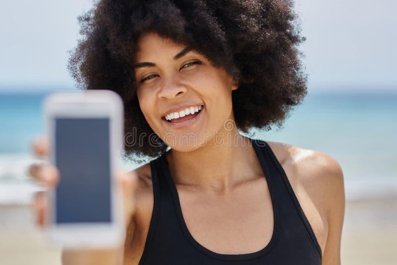 Glückliches afroes-amerikanisch Mädchen, das Handy hält lizenzfreie stockbilder