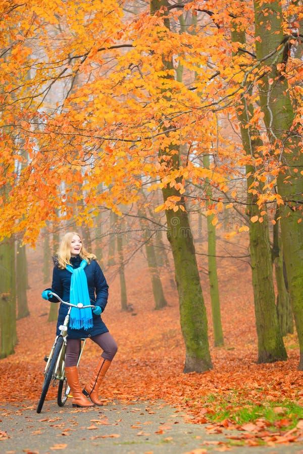 Glückliches aktives Frauenreitfahrrad im Herbstpark lizenzfreie stockbilder