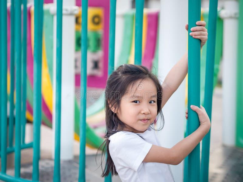 Glückliches asiatisches Babykind, das auf Spielplatz spielt lizenzfreie stockbilder
