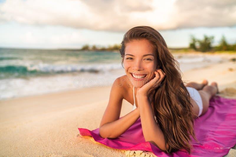 Glückliches asiatisches Bikini wwoman Modell, das auf den Sommerferien liegen auf Badetuch, Hawaii sich entspannt stockbilder