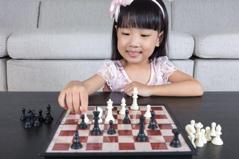 Glückliches asiatisches chinesisches kleines Mädchen, das zu Hause Schachschach spielt lizenzfreies stockfoto