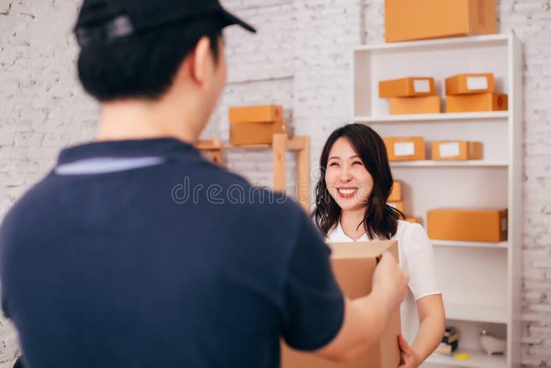 Glückliches asiatisches erwachsenes Geschäft weiblich im Büro, das ein Paket vom männlichen deliverman empfängt lizenzfreie stockbilder