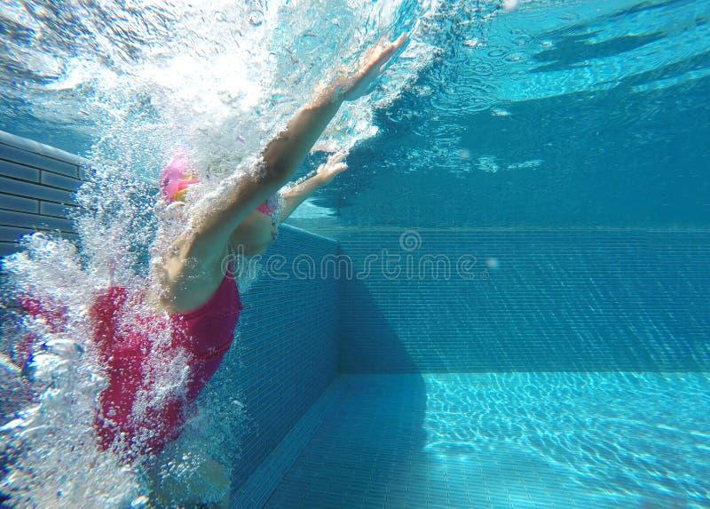 Glückliches asiatisches Kind, das unter Wasser im Sommer schwimmt stockbilder