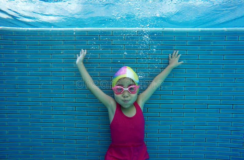 Glückliches asiatisches Kind, das unter Wasser im Sommer schwimmt stockfoto