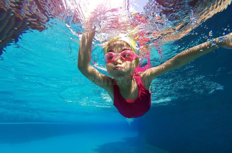 Glückliches asiatisches Kind, das unter Wasser im Sommer schwimmt lizenzfreie stockbilder