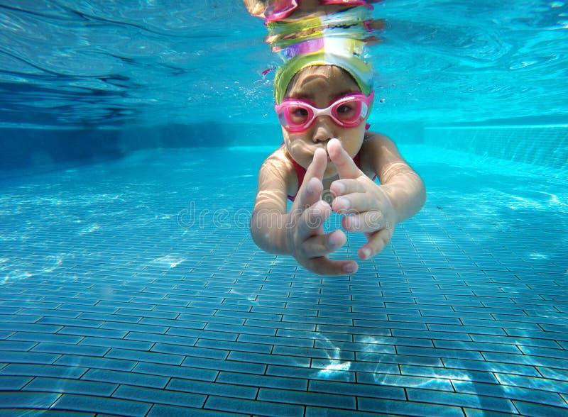 Glückliches asiatisches Kind, das unter Wasser im Sommer schwimmt stockfotografie